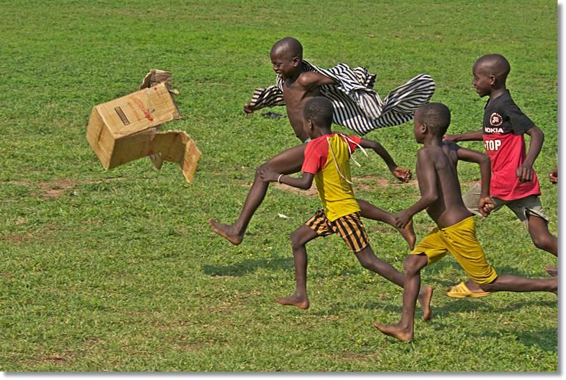 Niños ashanti jugando al futbol con una caja