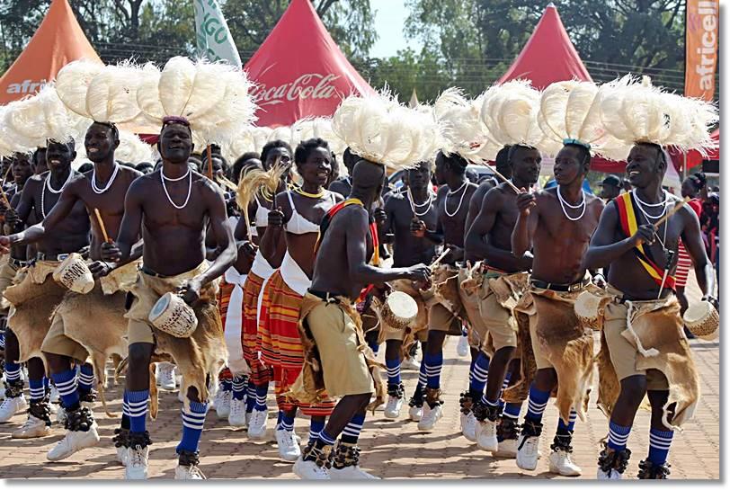 Acholis con plumas de avestruz y una piel de leopardo, ejecutando una danza ritual.